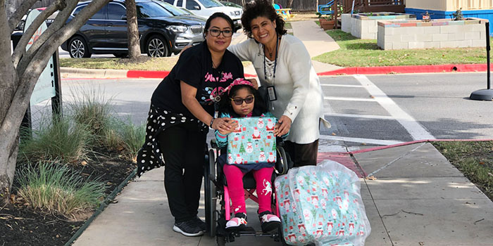 Young girl and two women pose with holiday gifts