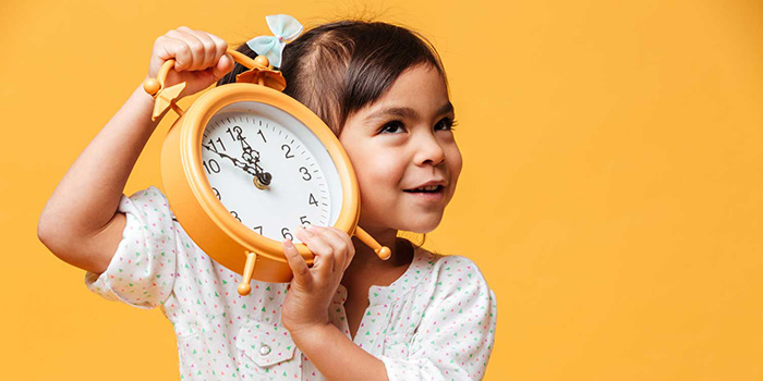 Girl holding up a clock
