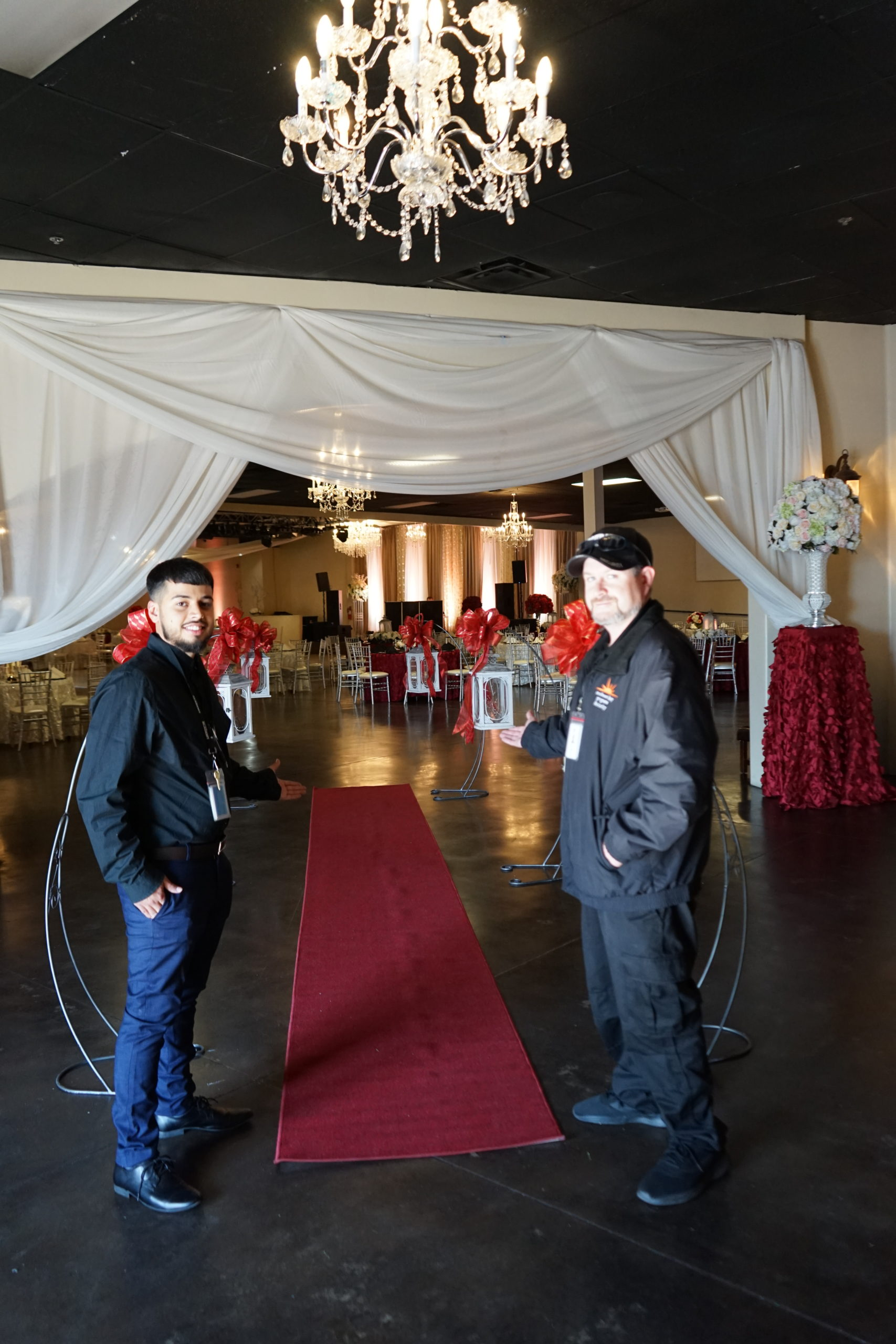 2 men posing in front of the red carpet entrance for SWK quinceanera