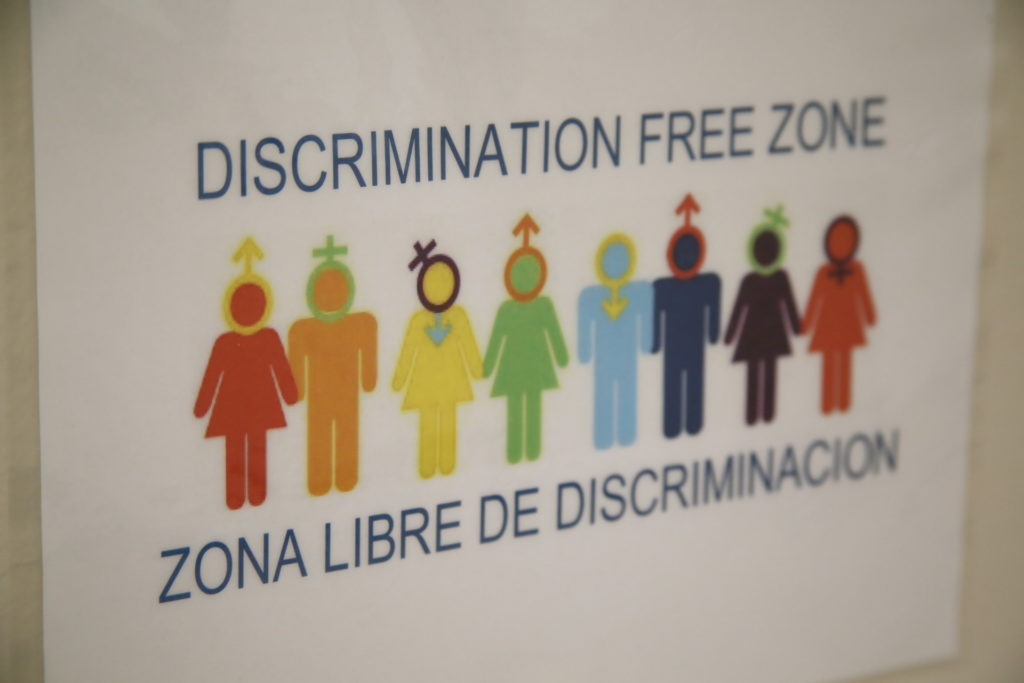 "a poster showing rainbow-colored people symbols with the text ""Discrimination free zone"" in English and Spanish"