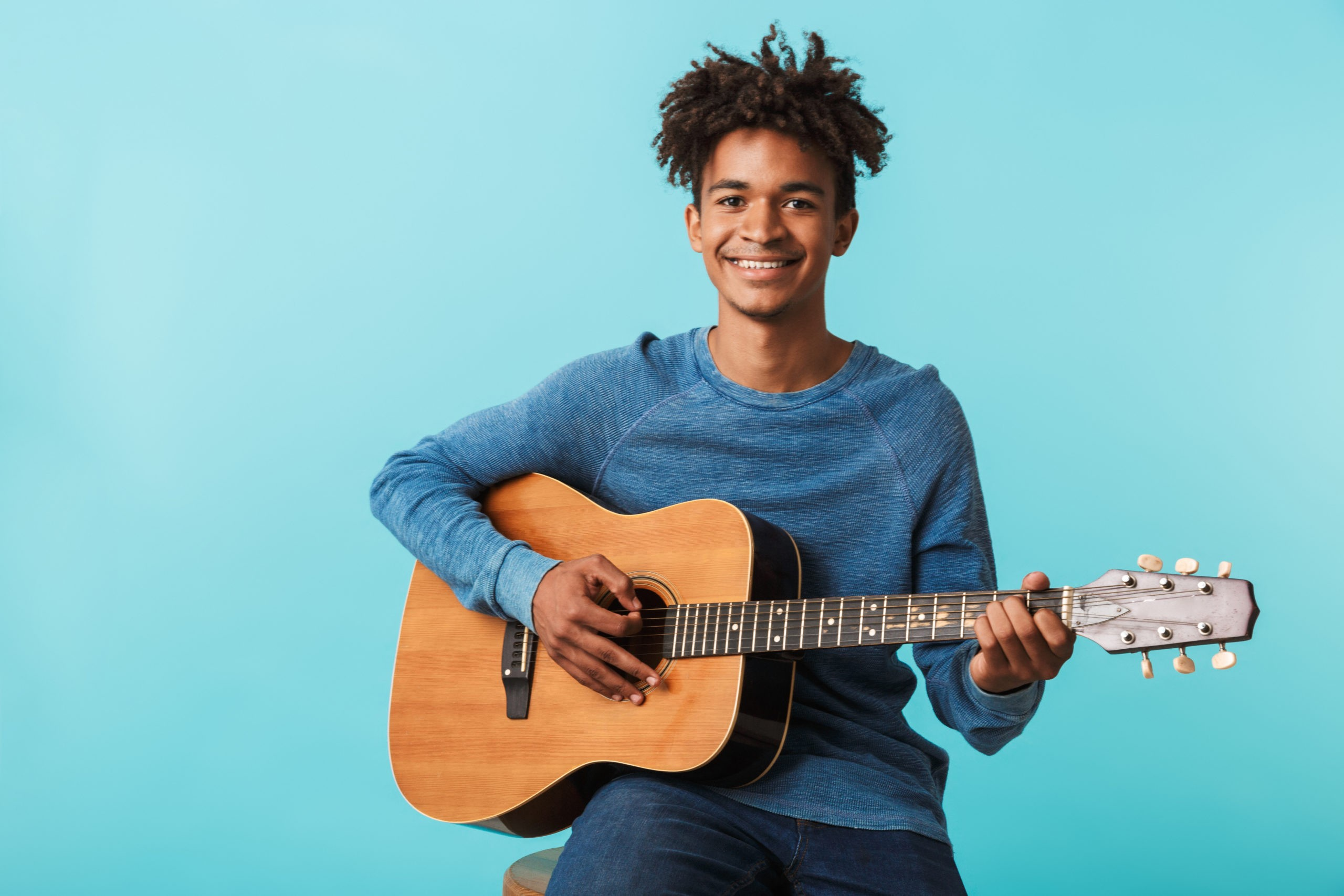 Boy sitting with a guitar in hand