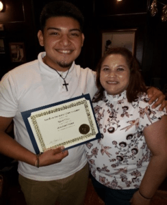 Ryan Flores receiving a certificate with a loved one.