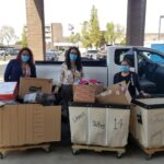 Three people with 3 carts of donations