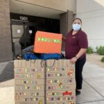 Person posing next to donations for migrant workers