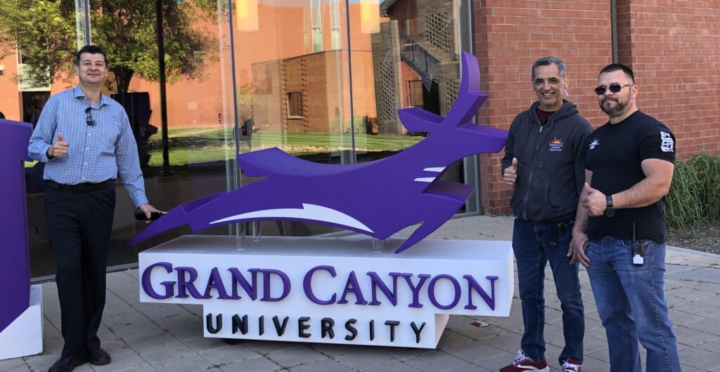 Dr Noe Vargas and SWK employees pose in front of GCU sign